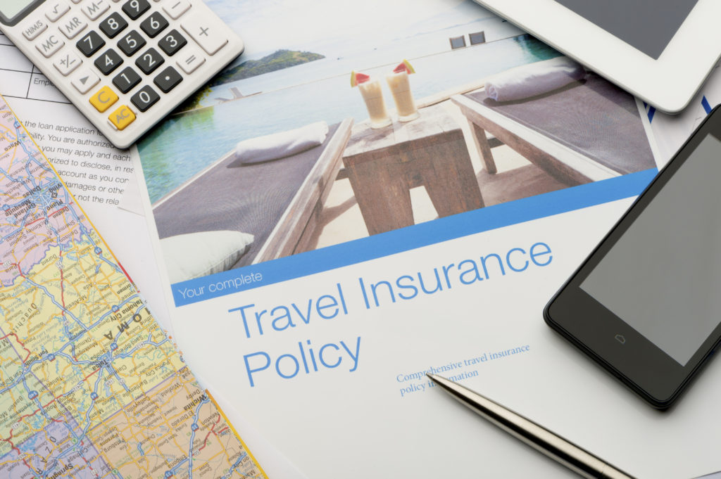 Travel insurance policy document with paperwork and technology